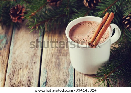 Cup of hot cocoa or hot chocolate on wooden background with fir tree and cinnamon sticks, traditional beverage for winter time, vintage toning - stock photo