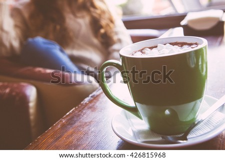 cup of hot cocoa with marshmallows on blue wooden background - stock photo