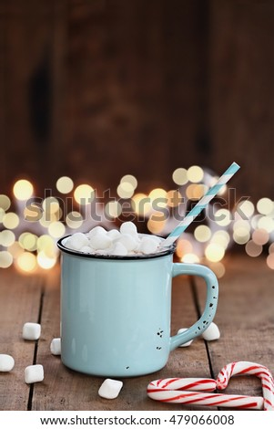 Cup of hot cocoa with mini marshmallows and candy canes in the shape of a heart over a wooden background with beautiful Christmas lights of bokeh. Could also be coffee. Perfect winter time treat.