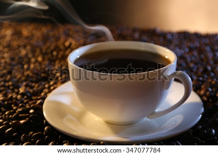 Cup of hot coffee among coffee beans on dark background - stock photo