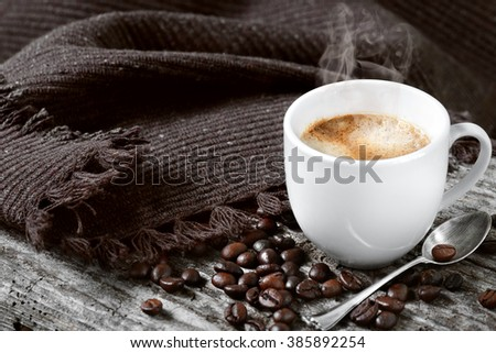 cup of hot coffee and beans on old wood - stock photo