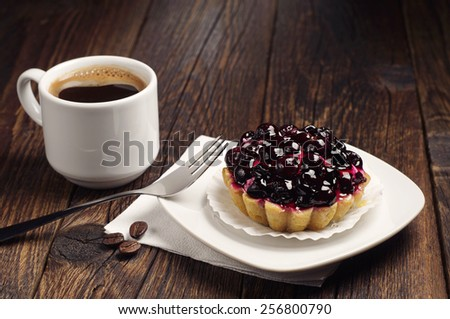 Cup of hot coffee and cake with black currants on dark wooden table - stock photo