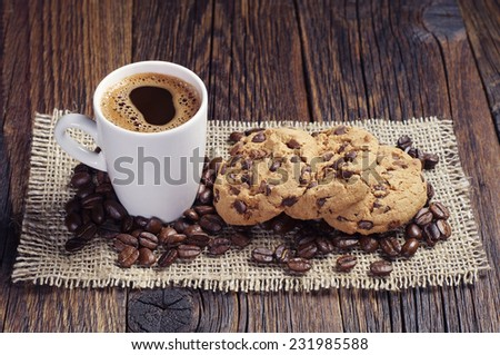 Cup of hot coffee and chocolate cookies on burlap  - stock photo