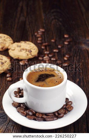 Cup of hot coffee and chocolate cookies on vintage wooden table
