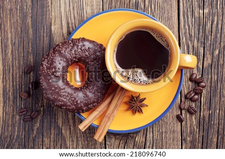 Cup of hot coffee and chocolate donut on vintage wooden background. Top view - stock photo