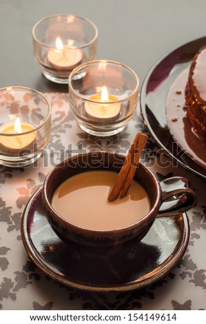 Cup of hot coffee and cinnamon with candlelight on the table. - stock photo