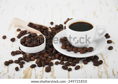 Cup of hot coffee and coffee beans on a wooden table  - stock photo