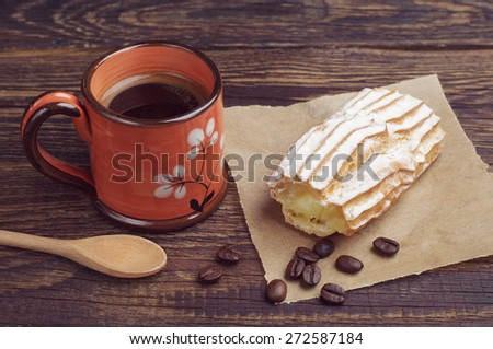 Cup of hot coffee and delicious cake with creamy on dark table   - stock photo