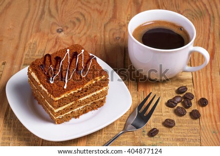 Cup of hot coffee and honey cake on old wooden table