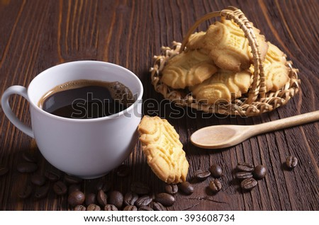 Cup of hot coffee and shortbread cookies on brown wooden table - stock photo