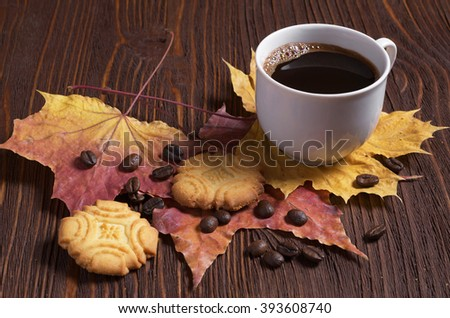 Cup of hot coffee and shortbread cookies on brown wooden table with autumn leaves - stock photo