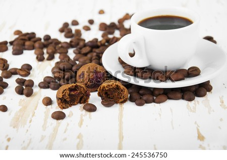 Cup of hot coffee and small cookies on wooden background - stock photo