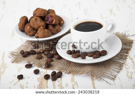 Cup of hot coffee and small cookies with spices on wooden background - stock photo
