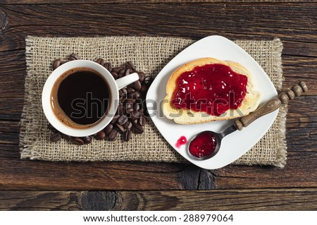 Cup of hot coffee and toasted bread with jam on old wooden table, top view - stock photo