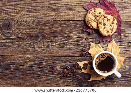 Cup of hot coffee, chocolate cookies and autumn leaves on a wooden background. Top view - stock photo