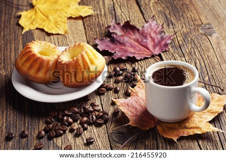 Cup of hot coffee, cupcake and autumn leaves on a wooden background