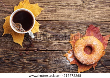 Cup of hot coffee, donut and autumn leaves on old wooden table. Top view - stock photo