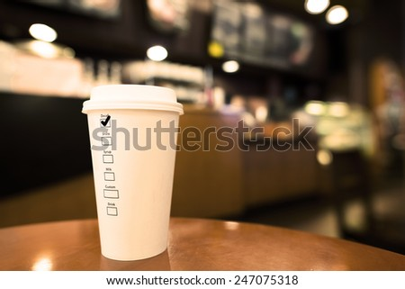 Cup of Hot Coffee on Wood Table. With Label on the Cup Tick on Decaf - stock photo