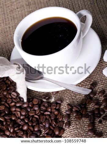Cup of hot coffee over cloth sack - stock photo