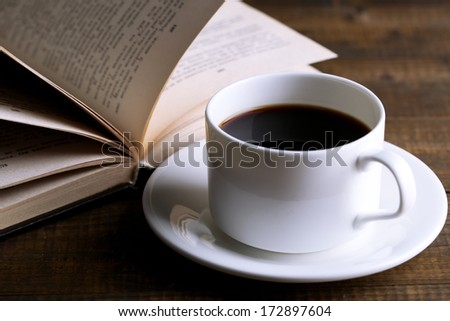 Cup of hot coffee with book on wooden background
