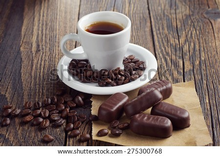 Cup of hot coffee with chocolates on dark wooden table - stock photo