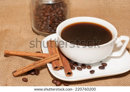 Cup of hot coffee with cinnamon sticks on vintage rustic background with muffins.