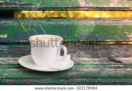 Cup of hot coffee with cream is on old wooden bench in autumn park.  Selective focus with shallow DOF - stock photo