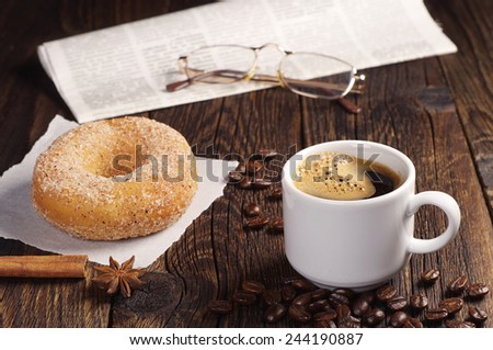 Cup of hot coffee with donut and newspaper on old wooden table