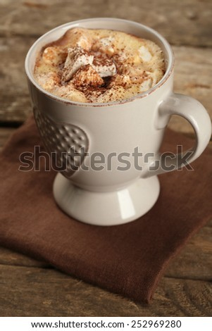 Cup of hot coffee with marshmallow on napkin and rustic wooden planks background