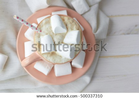 Cup of hot coffee with marshmallows on light background