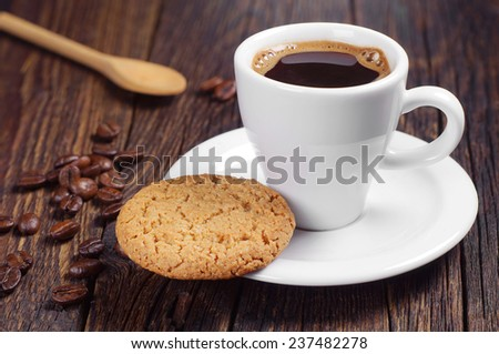 Cup of hot coffee with oatmeal cookie on dark wooden table