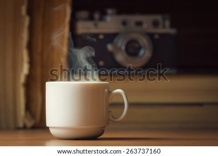 Cup of hot coffee with steam over defocused books and vintage camera - stock photo