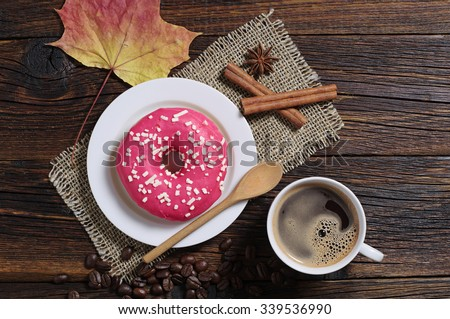 Cup of hot coffee with sweet donut for breakfast on old wooden table, top view  - stock photo