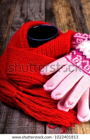 Cup of hot drink wrapped by red scarf and gloves on wooden board.Closeup