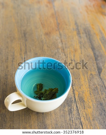 Cup of hot green tea  on wood table - stock photo