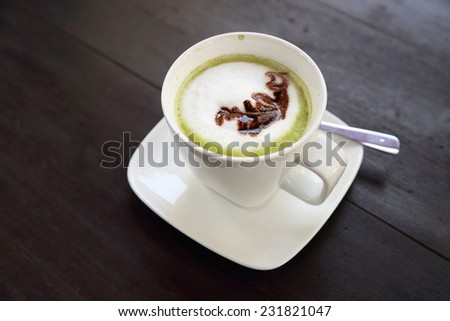Cup of hot matcha green tea latte with milk cream