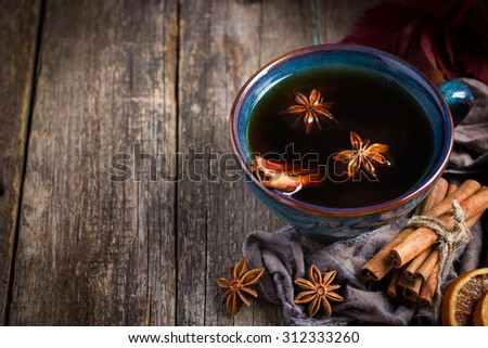 Cup of hot spicy tea with anise and cinnamon, selective focus, copy space - stock photo