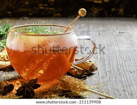 Cup of hot sweet spiced tea or gluhwein for celebrating the Christmas season surrounded by dried aromatic spices - cinammon and star anise - and caramelized sugar - stock photo