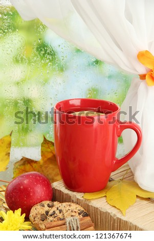 cup of hot tea and autumn leaves, on rain background - stock photo