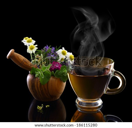 Cup of hot tea and mortar with fresh herbs - stock photo