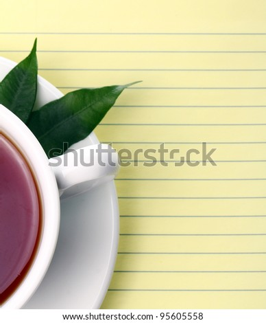 Cup of hot tea and notebook - stock photo