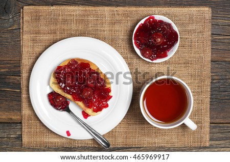 Cup of hot tea and roasted white bread with cherry jam for breakfast, top view