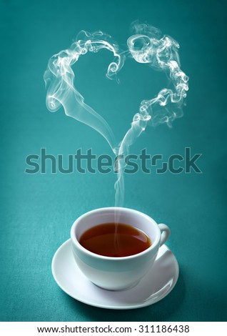 Cup of hot tea on the emerald green background - stock photo