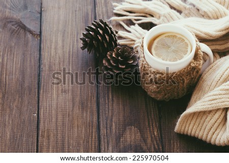 Cup of hot tea with lemon dressed in knitted warm winter scarf on brown wooden tabletop, top view point - stock photo