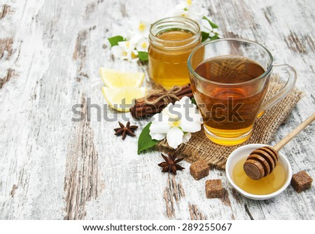 Cup of jasmin tea with honey on a wooden background