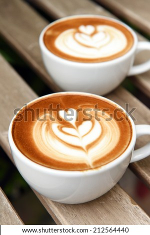 cup of latte art coffee on table - stock photo