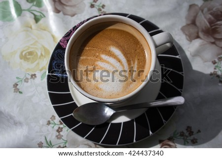 Cup of latte art coffee with froth butterfly - stock photo