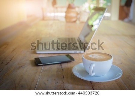 Cup of latte art, laptop and smart phone on wooden table.