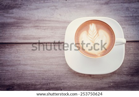 cup of latte coffee on the wood background with retro filter effect - stock photo