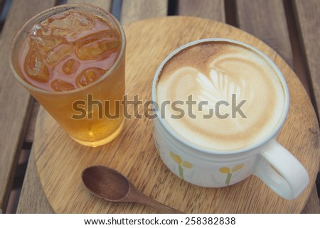 Cup of latte coffee with cold tea on wooden tray